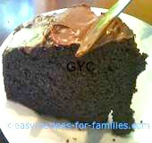 A slice of cake from easy chocolate cake recipes, with frosting being spread
