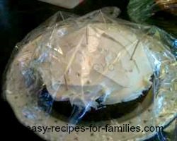 pumpkin cake covered with Cling Wrap supported on toothpicks