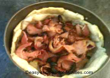 Cooked bacon in the base of the pastry shell