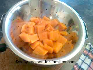 Stewed pumpkin draining in a colander, in the process of making pumpkin puree