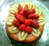 A pumpkin pie cake decorated with strawberries and kiwi Fruit