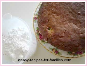 sultana cake with a jug of icing sugar