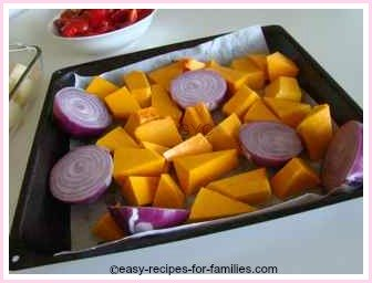 roasting tray with onions and pumpkin ready for roasting