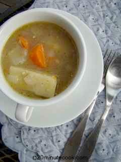 Serving of chicken soup in a large tea cup and saucer